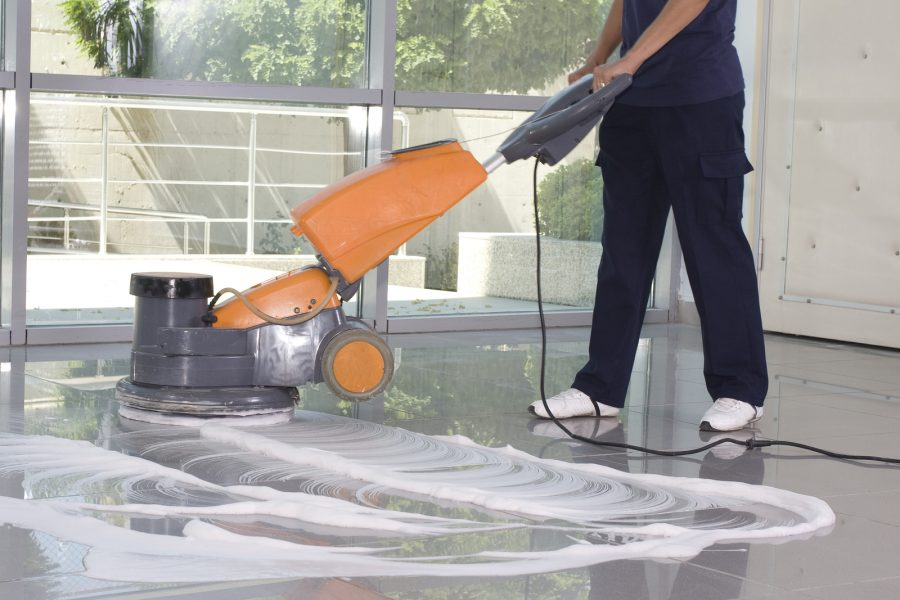 a worker is cleaning the floor with equipment